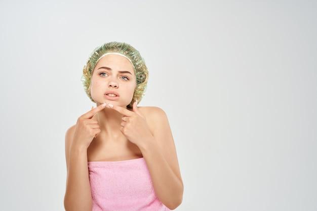 Mulher touca de banho espreme acne no rosto, cuidados com a pele