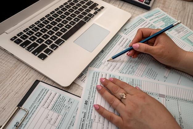 Mulher trabalha com formulário de imposto de eua 1040 e laptop calculadora no escritório. conceito de contabilidade