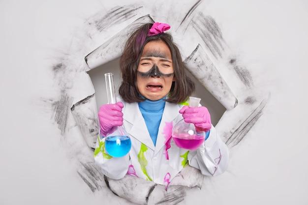 Mulher trabalha como química segura frascos de vidro de teste com solidão colorida chateada com resultados de experimento usa jaleco médico rasgando papel