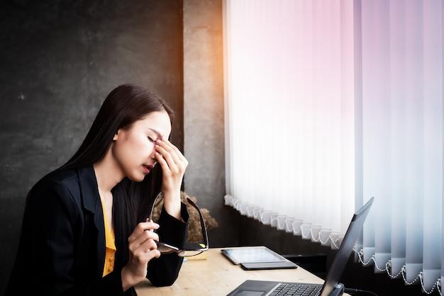 Mulher trabalha duro, coloca a mão para tocar o olho, fadiga, olhos queimam usando laptop