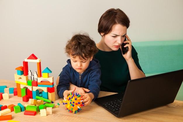 Mulher trabalha em casa com uma criança. a mãe se senta atrás de um laptop enquanto a criança brinca e faz um coronavírus simulado, além de construir uma casa de cubos para a família.