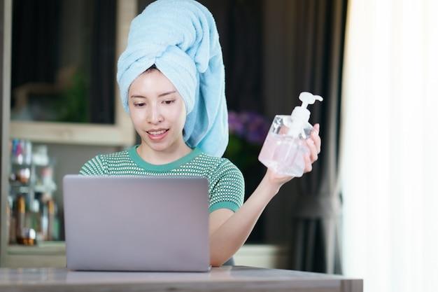 Mulher trabalha em casa em quarentena para coronavírus usando máscara protetora e limpando as mãos com gel desinfetante.