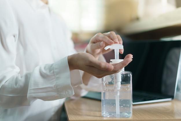 Mulher trabalha em casa em quarentena por coronavírus usando máscara protetora e limpando as mãos com gel desinfetante