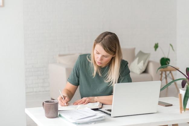Mulher trabalha ou aprende em casa com um caderno, escrevendo à mesa