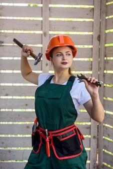 Mulher trabalhadora com ferramentas. jovem de macacão e capacete posando no canteiro de obras