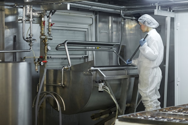Mulher trabalhadora de grande angular usando a máquina de mistura na fábrica de produção de alimentos limpos, copie o espaço