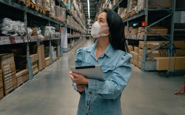 Mulher trabalhadora de negócios asiáticos usa máscara usando tablet digital, verificando o estoque de produtos no armazém