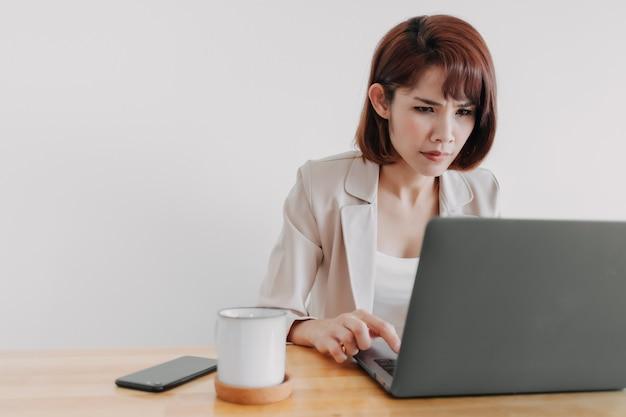 Mulher trabalhadora está usando o laptop na mesa do escritório com fundo branco