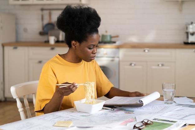 Mulher trabalhadora freelance ocupada que lê documentos e come no escritório em casa, sente-se à mesa na cozinha com pressa