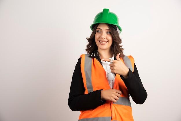 Mulher trabalhadora industrial apontando para branco