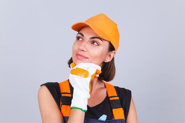 Mulher trabalhadora pintora de macacão e luvas na parede cinza feliz sorriso positivo e pensativo olhar de lado