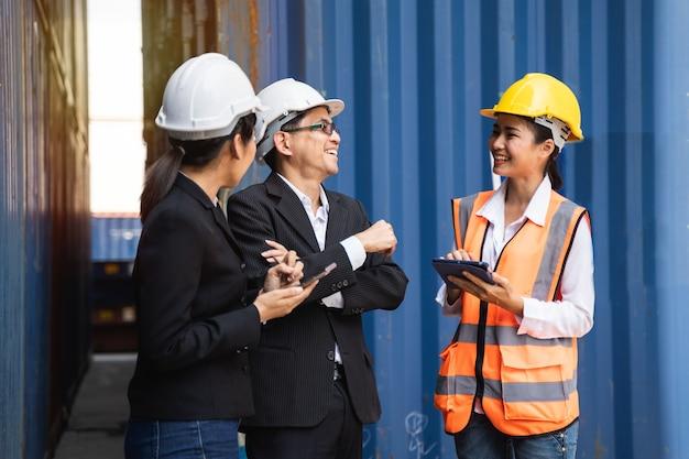 Mulher trabalhadora trabalhando com foreman, segurando um capacete amarelo para controlar o carregamento e verificar a qualidade dos contêineres do navio de carga para importação e exportação no estaleiro ou porto