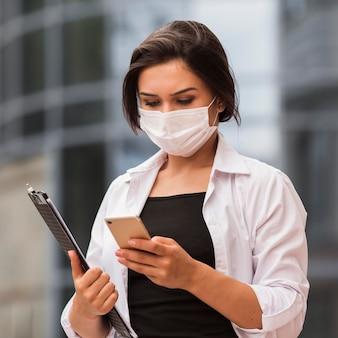 Mulher trabalhando ao ar livre com smartphone e bloco de notas durante a pandemia