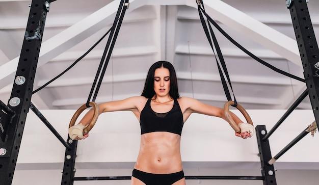 Mulher trabalhando com anéis de ginástica na academia cross fit
