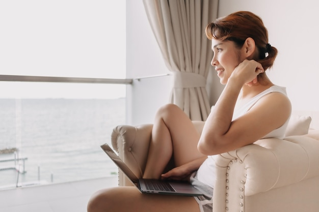 Mulher trabalhando com laptop e relaxando no sofá do hotel