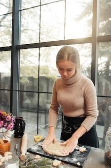 Mulher trabalhando com massa de pão de gengibre na cozinha