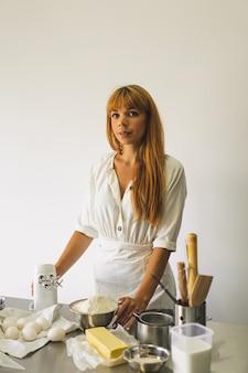 Mulher trabalhando com receita de preparação de massa, pizza de pão ou torta fazendo ingredientes cozinhando bolos