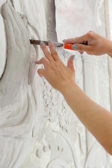 Mulher trabalhando com uma ferramenta cinzel esculpindo o padrão de baixo-relevo na parede