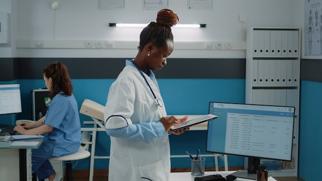 Mulher trabalhando como médica e segurando um tablet digital