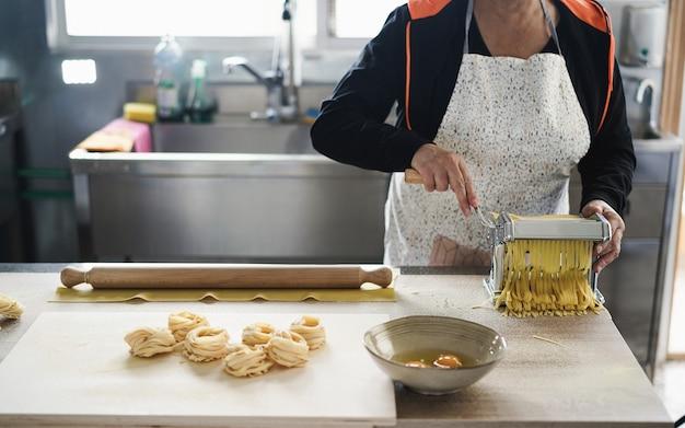 Mulher trabalhando dentro de uma fábrica de massas - massa fresca tradicional italiana e conceito de pequena empresa
