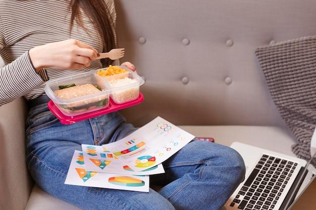 Mulher trabalhando e comendo em um sofá