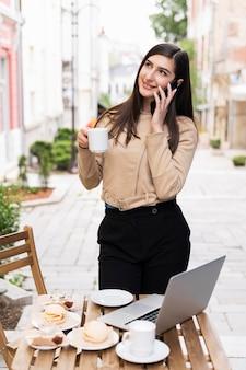 Mulher trabalhando e tomando café ao ar livre