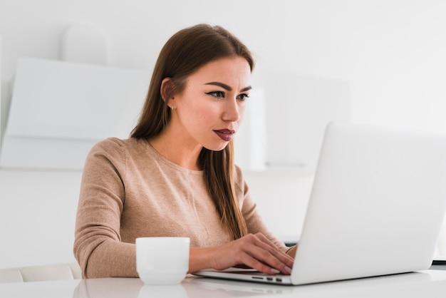 Mulher trabalhando e tomando uma xícara de café