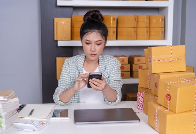 Mulher, trabalhando, e, verificar, ordem produto, com, smartphone, em, escritório lar