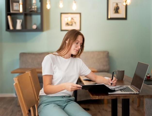 Mulher trabalhando em casa com um laptop durante a pandemia