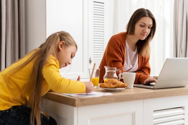 Mulher trabalhando em casa com uma garota mediana