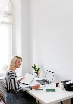 Mulher trabalhando em casa com vista lateral