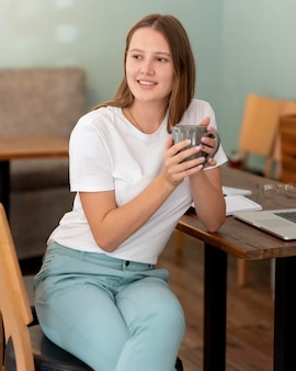 Mulher trabalhando em casa durante a pandemia enquanto toma café
