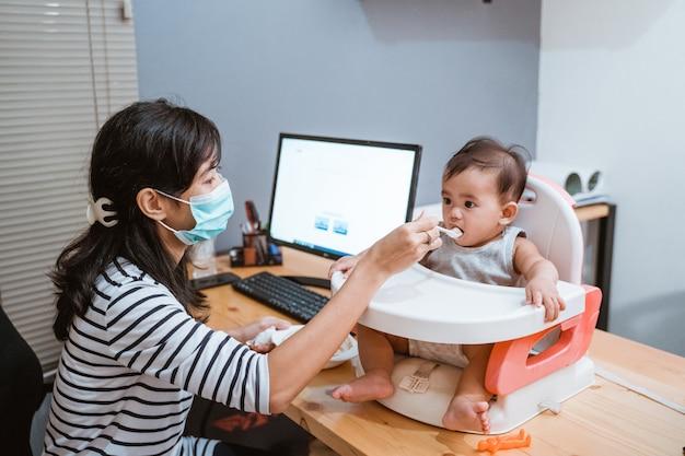 Mulher trabalhando em casa e cuidando de seu bebê
