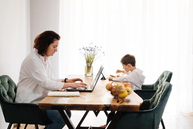 Mulher trabalhando em casa em um laptop enquanto uma criança comendo com um tablet