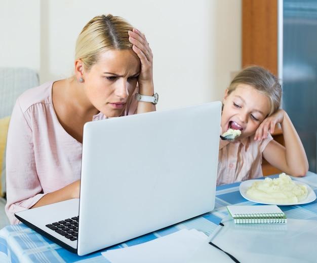Mulher trabalhando em casa, filha pequena, pedindo atenção