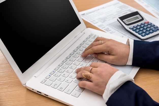 Mulher trabalhando em laptop e preenchendo formulário fiscal
