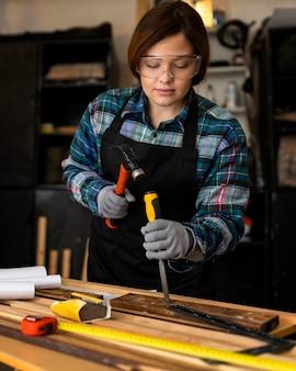 Mulher trabalhando em oficina com pranchas de madeira