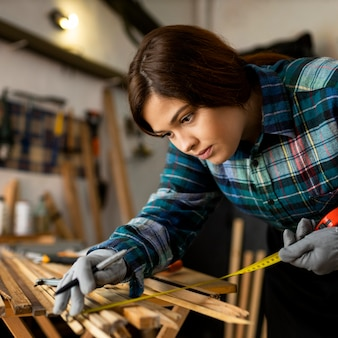 Mulher trabalhando em oficina medindo pranchas de madeira