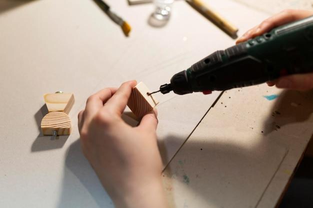 Mulher trabalhando em pedacinhos de madeira