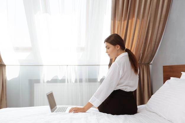 Mulher trabalhando em quarto de hotel