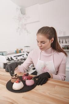 Mulher trabalhando em sua cafeteria decorando sobremesas deliciosas