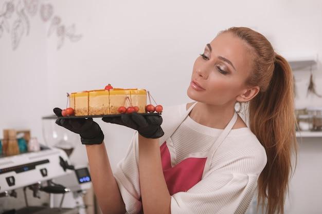 Mulher trabalhando em sua confeitaria vegana crua, examinando um delicioso bolo de manga