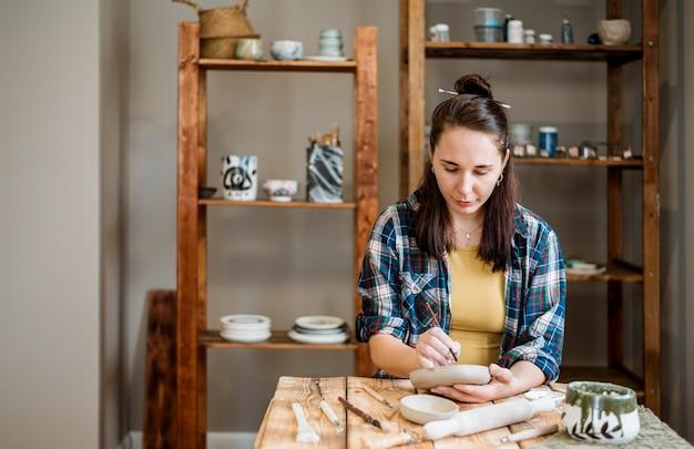 Mulher trabalhando em sua oficina de cerâmica