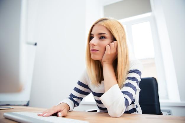 Mulher trabalhando em um computador desktop no escritório