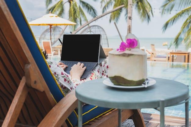 Mulher trabalhando em um laptop à beira da piscina nas férias