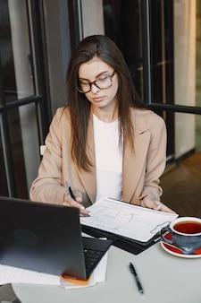 Mulher trabalhando em um laptop em um café de rua. vestindo roupas elegantes e elegantes - jaqueta, óculos