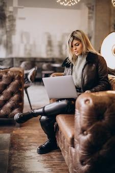 Mulher trabalhando em um laptop em um café e sentada no sofá