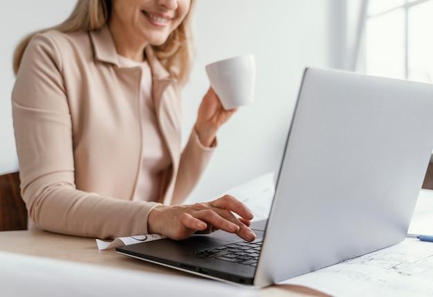 Mulher trabalhando em um laptop enquanto segura uma xícara de café