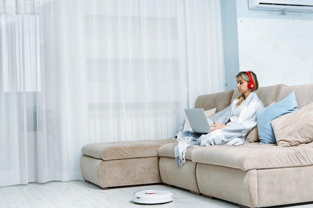 Mulher trabalhando em um laptop enquanto um aspirador de pó robô está sendo limpo