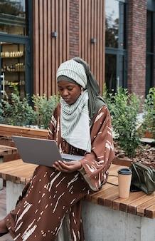 Mulher trabalhando em um laptop na cidade
